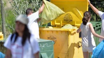 Voluntarios tiran bolsas de basura extraída en la batida de la Laguna del Campillo (Madrid).