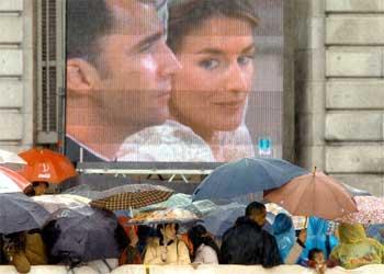Un corro de verdaderos entusiastas rodea, paraguas en mano, una de las cuatro pantallas gigantes colocadas en la plaza.