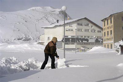 Una mujer quita nieve con una pala a la entrada de su tienda, hoy junto al paso fronterizo del Portalet.