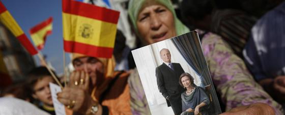 Miles de personas, con banderines y fotografías de los reyes, se han concentrado en la ciudad autónoma para recibir a Don Juan Carlos y Doña Sofía.