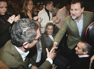 El presidente del PP, Mariano Rajoy, saluda al alcalde de Madrid, Alberto Ruiz-Gallardón, en el primer acto público tras la exclusión de éste último de las listas al Congreso