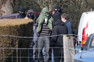Efectivos de la Gerdarmería francesa sacan, exposado y con la cara cubierta por una chaqueta verde, a uno de los tres miembros de ETA detenidos en la localidad de Cahan.