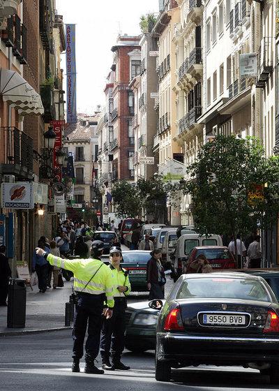 Unos agentes regulan el tráfico en el barrio de Las Letras de Madrid.