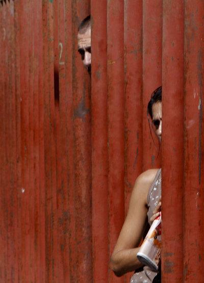 Un hombre y una mujer se asoman por una de las vallas que protegen los encierros.