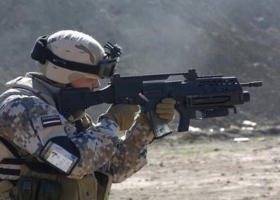 Soldado letón dispara un fusil de asalto Hk