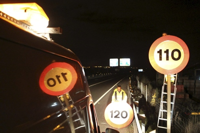 A worker changes the road sign on the A-55 motorway in Madrid.