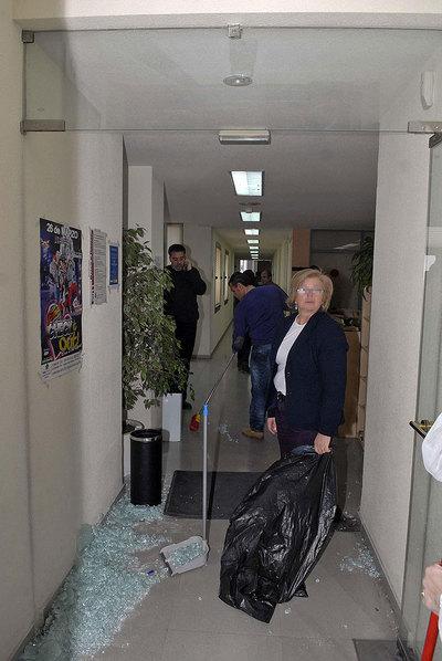 Funcionarios del Ayuntamiento de Valdemoro recogen los cristales tras la rotura de la puerta en la protesta de los bomberos.