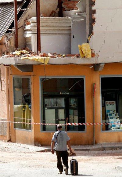 En la imagen, un vecino camina con su maleta por una calle del barrio de La Viñas de Lorca, afectado por el terremoto del 11 de mayo.