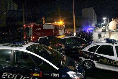 Miembros de la Policía Nacional y del cuerpo de bomberos bloquean la zona donde el joven falleció al caer a una hoguera.