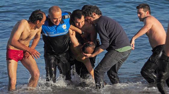 Agentes de la Policía Local retiran del agua al hombre de origen argelino, de 42 años de edad, que falleció tras ser rescatado esta mañana inconsciente de la playa del Orzán, en La Coruña, donde se había celebrado la noche de San Juan.