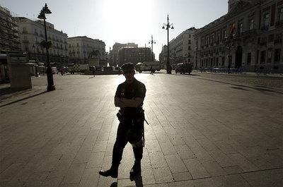 Un policía vigila esta mañana la Puerta del Sol, de donde ayer fueron desalojados los indignados.