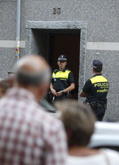 Miembros de la Policía municipal custodian la vivienda donde han sido hallados muertos con signos de violencia un matrimonio de unos 70 años, en el distrito madrileño de Puente de Vallecas.