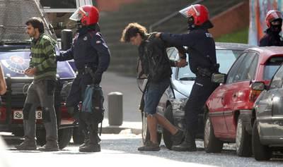 Dos agentes de la Ertzaintza conducen a dos de las 23 personas que ocupaban el 'gaztetxe' (local juvenil) Kukutza, ubicado en el barrio bilbaíno de Rekalde.
