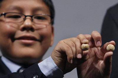 Un niño de San Ildefonso muestran la bola del número 58.268, premiado con el Gordo del sorteo de Navidad