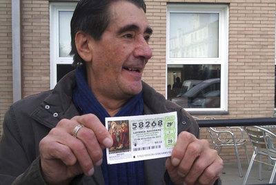 Un hombre, en un bar de Huesca, muestra su décimo premiado con el 'Gordo'.