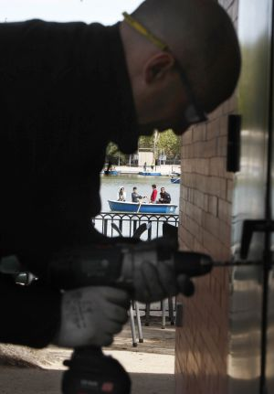 A municipal workman breaks the lock to the door of a quiosco before padlocking it shut.