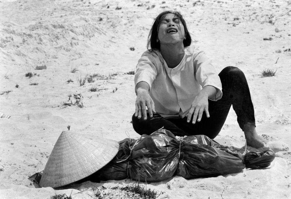 Una vietnamita llora sobre el cadáver de su marido, encontrado junto a otros 47 cuerpos en una fosa común en Hue, Vietnam.