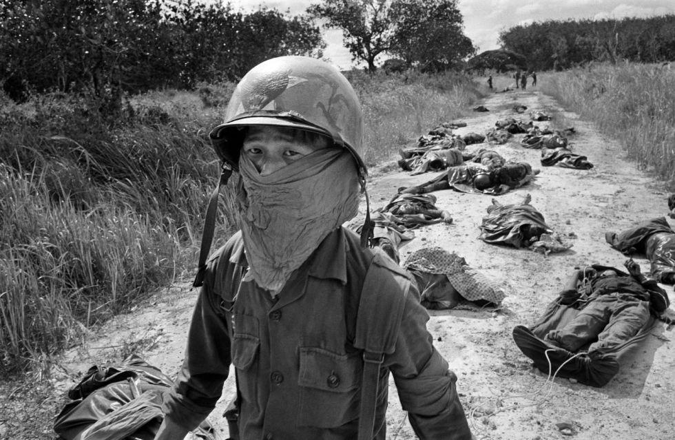 Un soldado de Vietnam del Sur se cubre la cara con un pañuelo para aguantar el olor de los cuerpos de varios soldados muertos en una emboscada del Viet Cong, el 27 de noviembre de 1965.