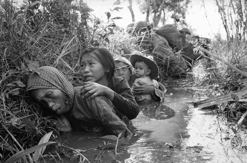 Mujeres y niños, atrapados en una trinchera en medio del fuego cruzado entre posiciones estadounidenses y del Viet Cong en la localidad de Bao Trai, el 1 de junio de 1966.