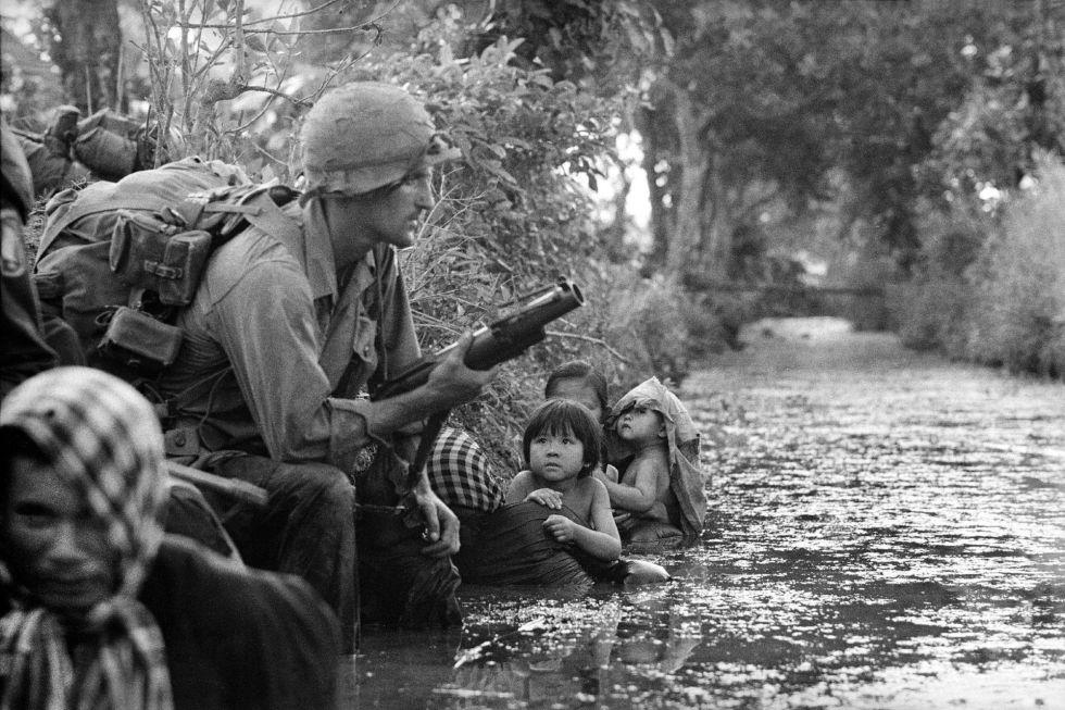 Dos niños, en brazos de dos mujeres, miran a un soldado estadounidense que porta un lanzagranadas M79, mientras se refugian del fuego del Viet Cong, en una imagen tomada el 1 de enero de 1966.