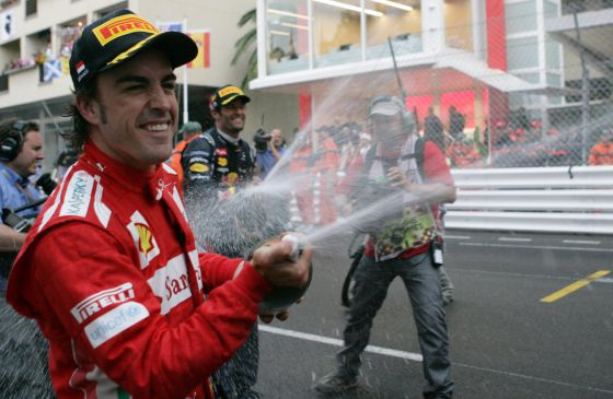 Ferrari's Spanish driver Fernando Alonso and Red Bull Racing's Australian driver Mark Webber  spray champagne at the Circuit de Monaco.