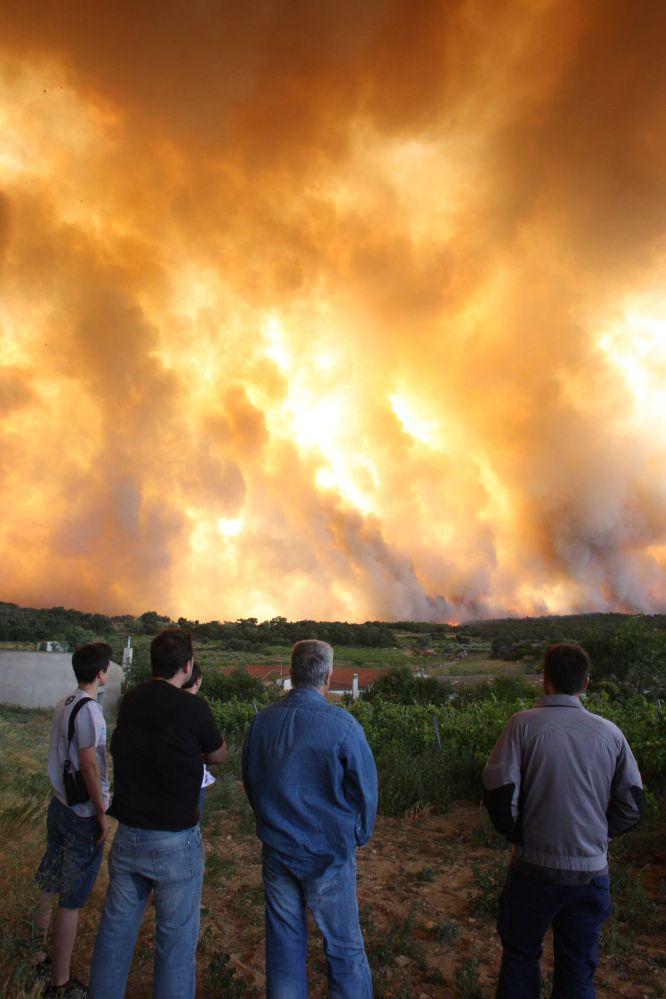 Un grupo de personas observa el fuego que avanza con fuerza por la zona de La Jonquera (Girona) en direccion sur.