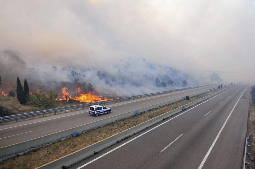 Un vehículo de la Policía Nacional circula por la AP-7 tras ser cortada como consecuencia del incendio forestal declarado en La Jonquera (Girona).
