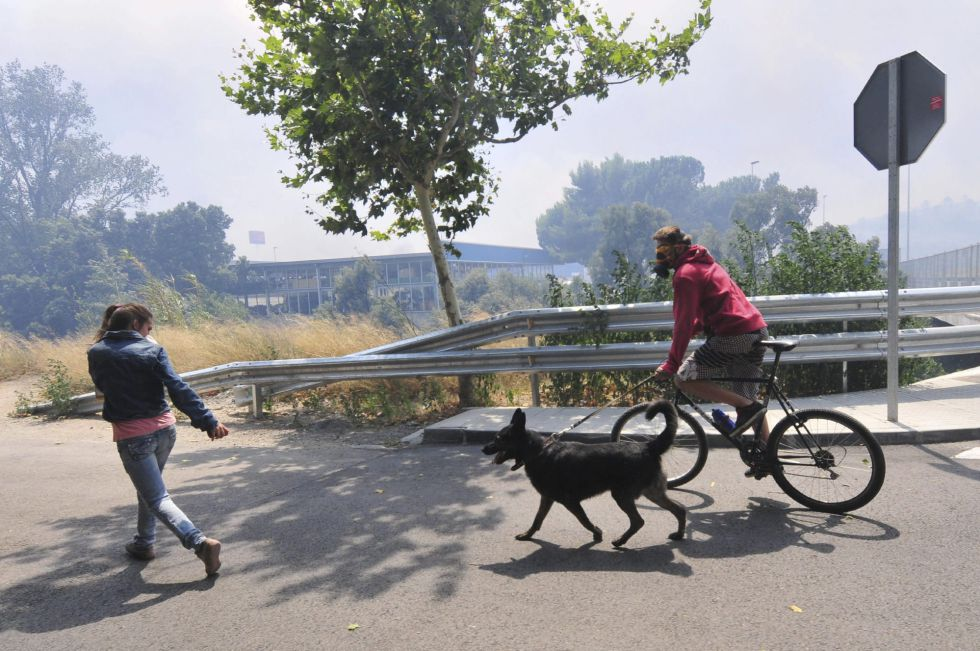 Dos vecinos con su perro con los rostros protegidos se alejan del incendio forestal declarado en La Jonquera (Girona).