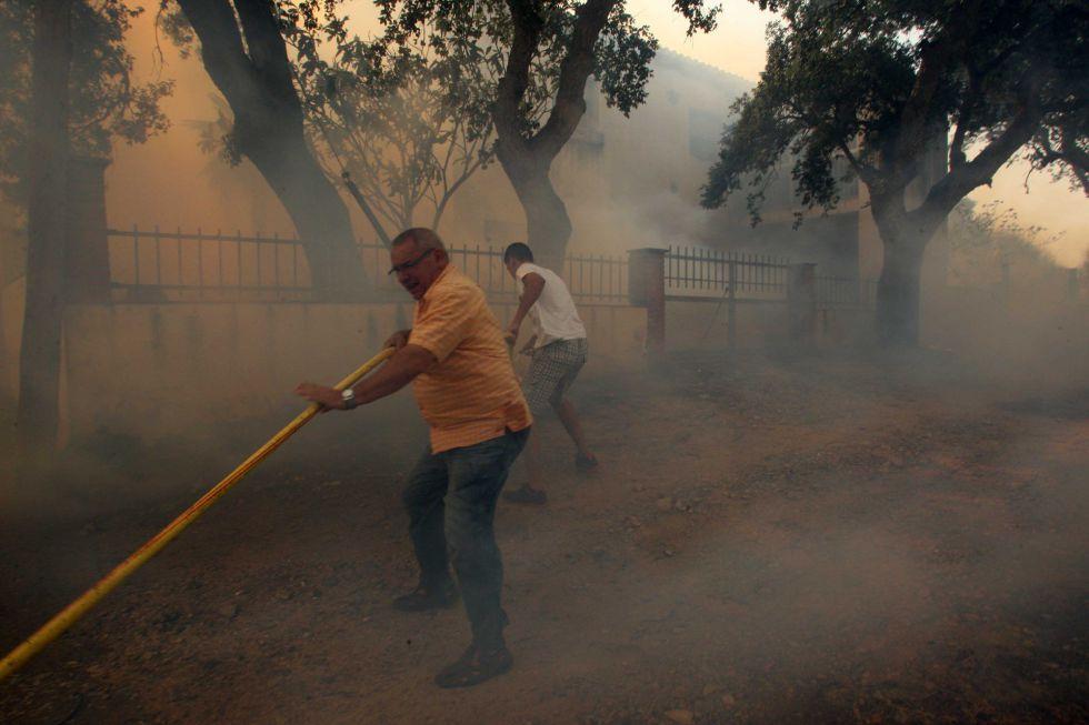 Unos vecinos intentan apagar el fuego junto a sus viviendas en la zona de Campmany (Girona).