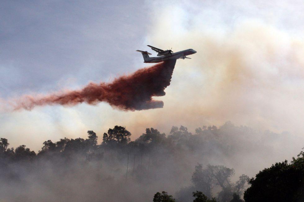 Un avión cisterna vierte agua sobre un incendio forestal cerca de la ciudad de Petrus, en la frontera con Francia.