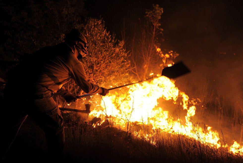 Un bombero intenta apagar las llamas cerca de La Jonquera en la madrugrada del lunes 23 de julio.