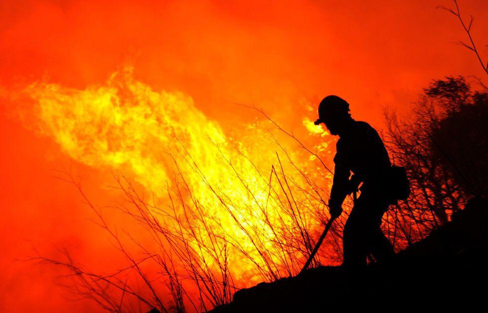 Un bombero intenta apargar el fuego cerca de La Jonquera (Girona) en la madrugada del lunes 23 de julio,