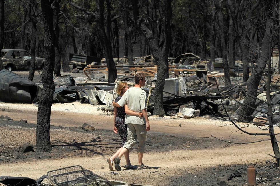 Una pareja pasea por el camping de Les Pedres, en la localidad de Capmany, arrasado por el fuego.