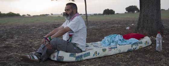 Juan Manuel Sánchez Gordillo sits on the mattress where he is sleeping on land owned by the Defense Ministry.