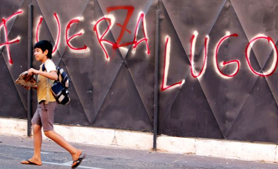"A boy passes in front of anti-Lugo graffiti with the words altered to read ""Power to Lugo."""