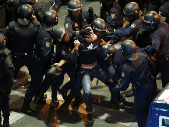 Riot police detain a protester during the protests in Madrid on Tuesday night.