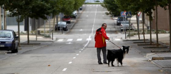 A man walks his dog in the deserted streets of Ciudad Valdeluz in the municipality of Yebes.