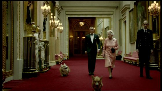 Isabel II y Daniel Craig camina por uno de los corredores del Palacio de Buckingham.