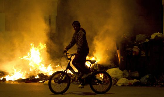 A child cycles past blazing trash cans in Jerez.