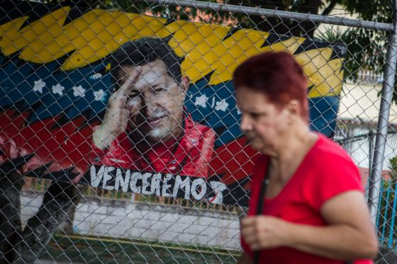A woman walks past an image of Hugo Chávez, who hasn't been seen in public for nearly a month.