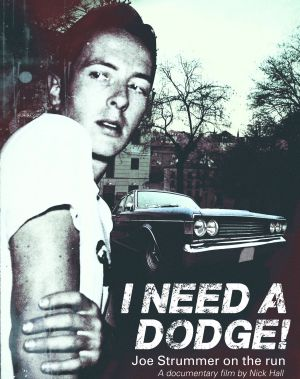 Clash frontman Joe Strummer with a Dodge in the background.