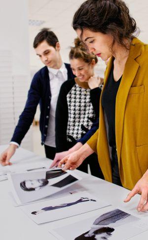 Varios trabajadores eligen las fotos de modelos que se incluirán en la página de la venta por Internet.