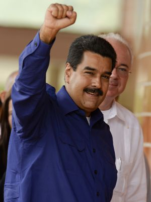 Venezuela's President Nicolás Maduro (l) gestures as he arrives for the opening of the Petrocaribe Summit, in Caracas on May 5.