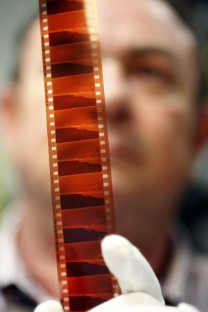 A Madrid Film employee checks a piece of celluloid.