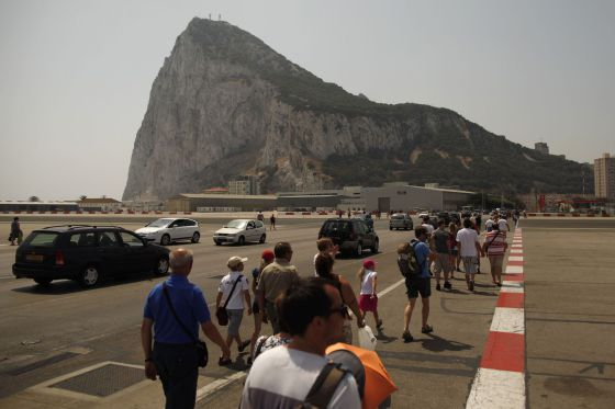 Pedestrians and drivers cross the tarmac of the Gibraltar airport in front of the Rock.