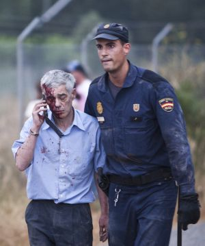 Francisco José Garzón Amo is led away from the crash site in Angrois, outside Santiago de Compostela.