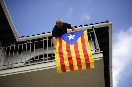 "A man hangs a ""Senyera"", the Independentist flag at his balcony  in Sant Pere de Torrello, near Barcelona Monday."