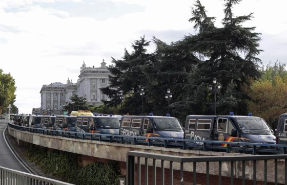 Police riot vans line the access road to the royal palace in Madrid Saturday.