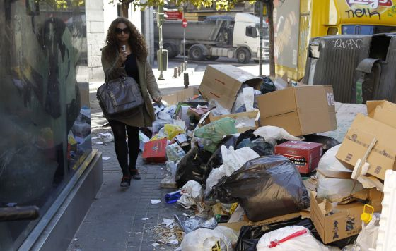 A woman walks past garbage piled up in Madrid's Amaniel street on Monday.