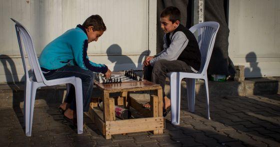 Dos adolescentes juegan una partida de ajedrez en el campo de Öncüpinar.